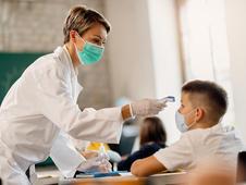 Enfermera escolar toma la temperatura del alumno de un colegio